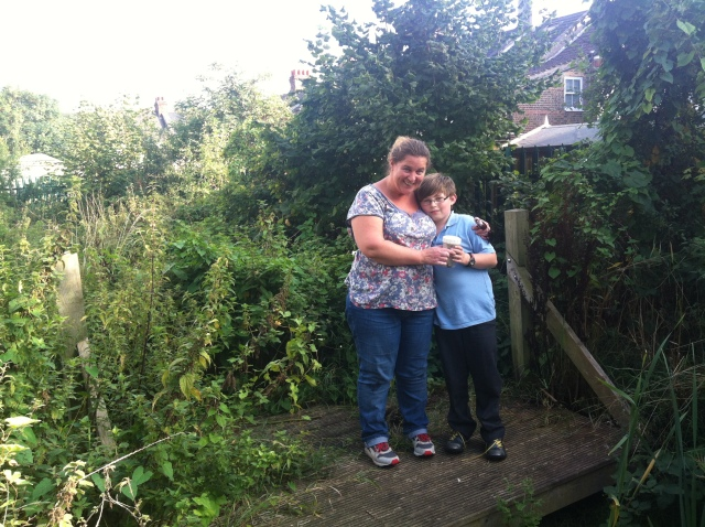 Sam and Shar stand in the Nature garden holding the container