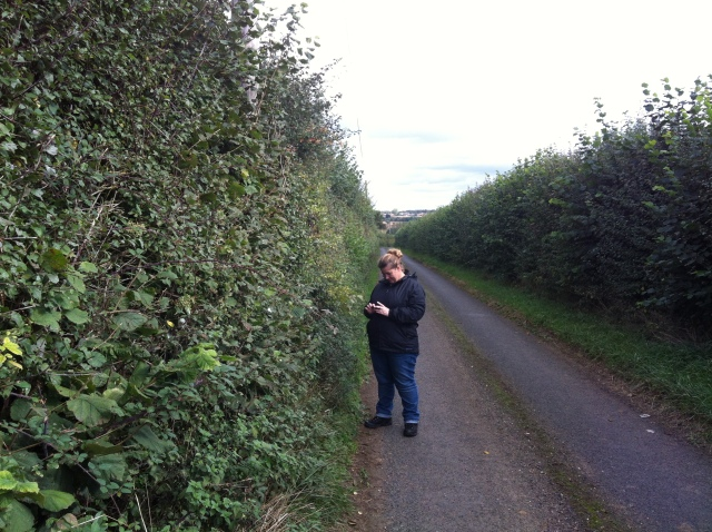 Shar is pictured standing in a lane that stretches off into the distance. A telegraph pole can be seen at the side of the lane which was the location of cache number 6