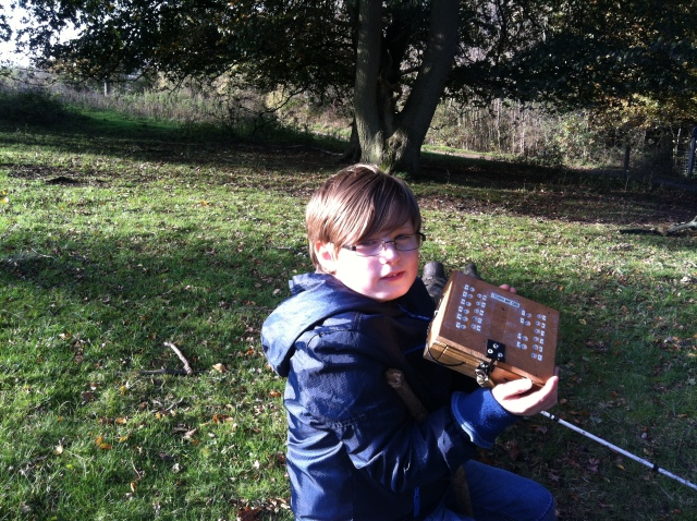 Sam is pictured on the log holding the puzzle box, a small wooden box sealed with a combination lock.