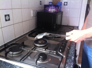 Holding the small plastic container with long Tongs I pass it through the flame on the hob to flash it