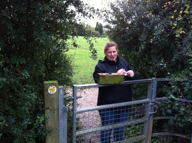 Shar is pictured at a kissing gate signing the log with the container, a sawn off piece of fence post balanced on the gate.