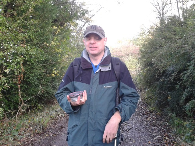Paul is pictured holding the 300th cache that team washknight has found. It is a normal runof the mill container, alas.
