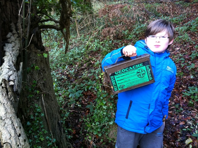 Sam is pictured holding an Ammo Can geocache container.