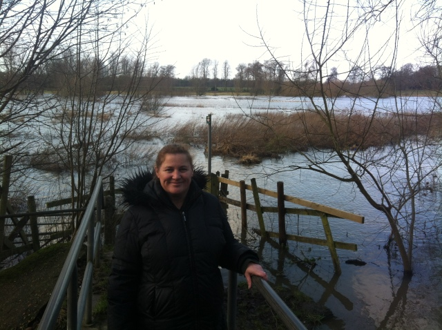 Sharlene smiles happily after finding a cache. She stands on a bridge with a view of fields in the background which are flooded due to the recent heavy rain causing the river to burst its banks.