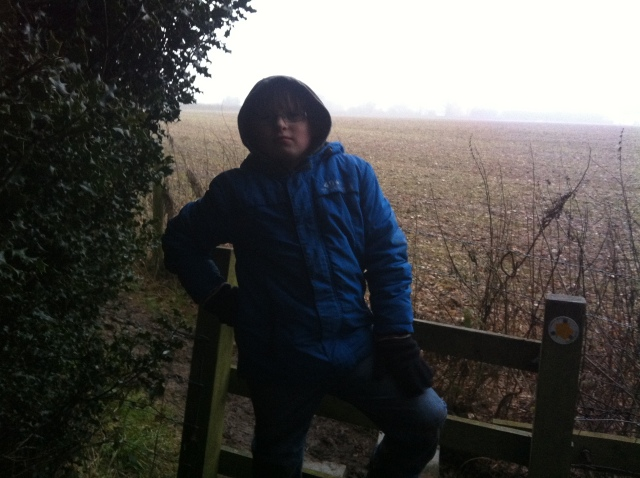 Sam is pictured on a stile with a very murky view across the fields in the background
