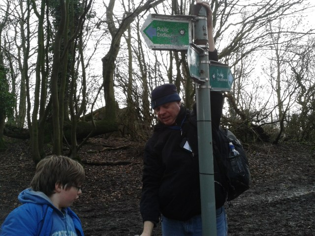 Sam stands at the ready with more water as Pauls is just about to pluck the floating cache from the top of the sign post. The draining water can just be seen expelling itself onto Paul's jacket.