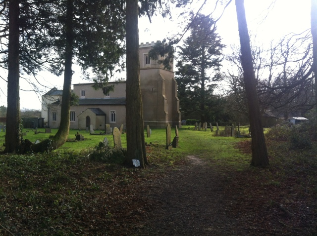 A view from the rear of the churchyard through the trees towards the small church.