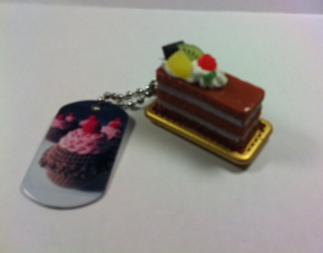 A small plastic slice of cake is attached by a short chain to a TravelBug tag ready to enter the BBH TB Race
