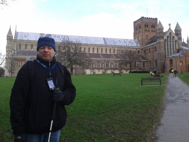 Paul stands to teh left of the frame with the imposing building of St. Albans Abbey dominating the rest of the picture
