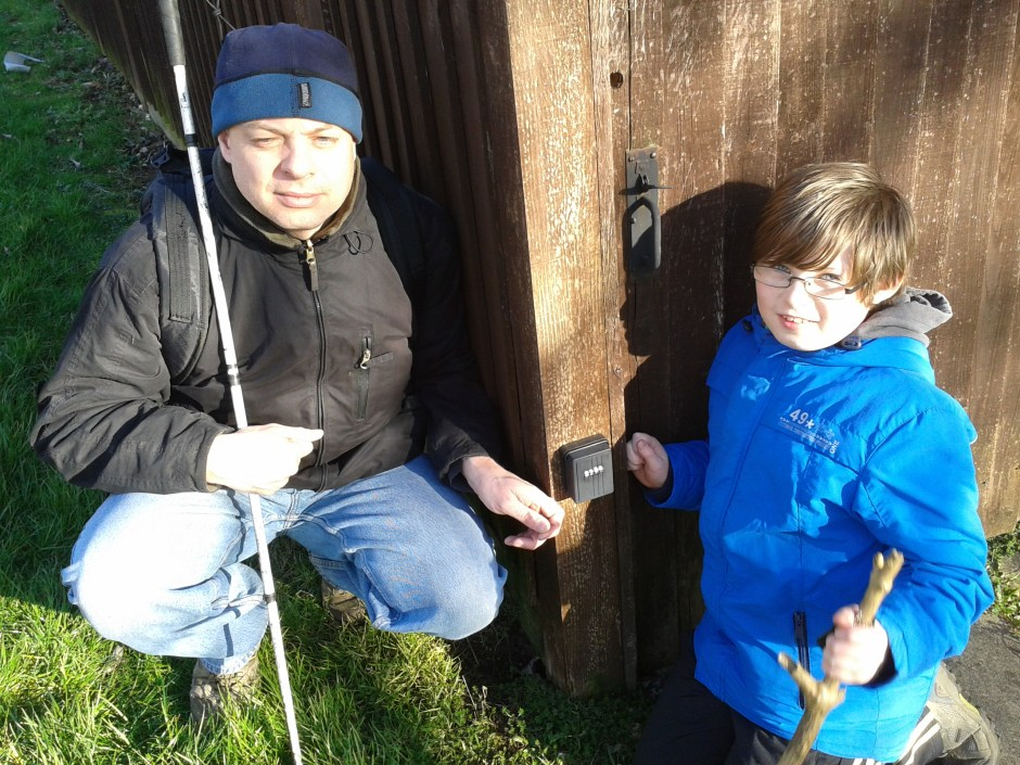 Paul is pictured squatting down next to the combination locked geocache container