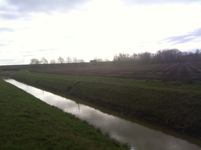 A channel of water stretches along the side of a field into the distance whilst the flat fnes stretch off to teh horizon