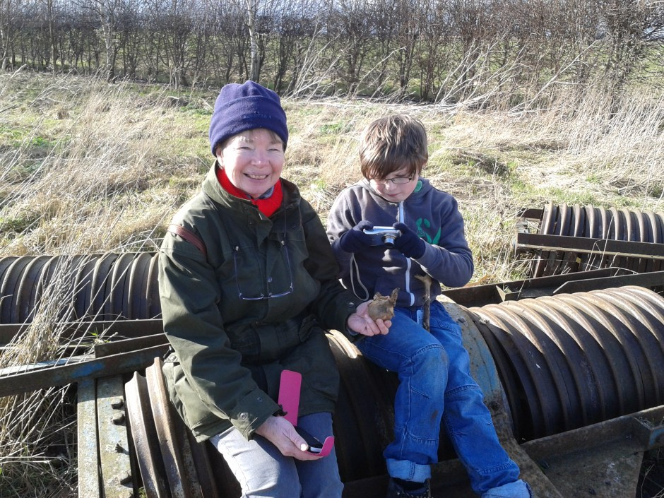 Sam and mum are pictured on the rusty farm machinery after finding the cache.