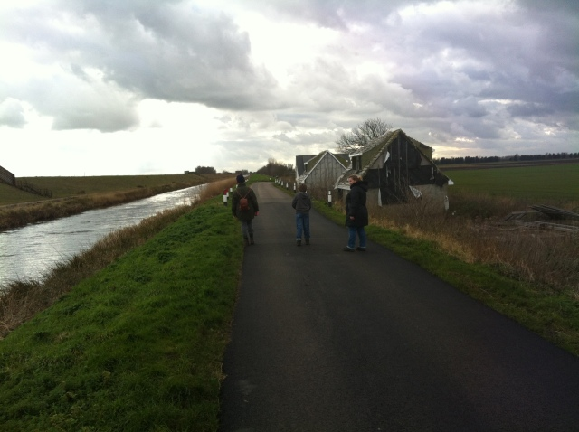 Sam, Shar and mum are pictured walking away from the camera down a long road that stretches off into the distance. The old Bedford River can be seen to the left flanking the road