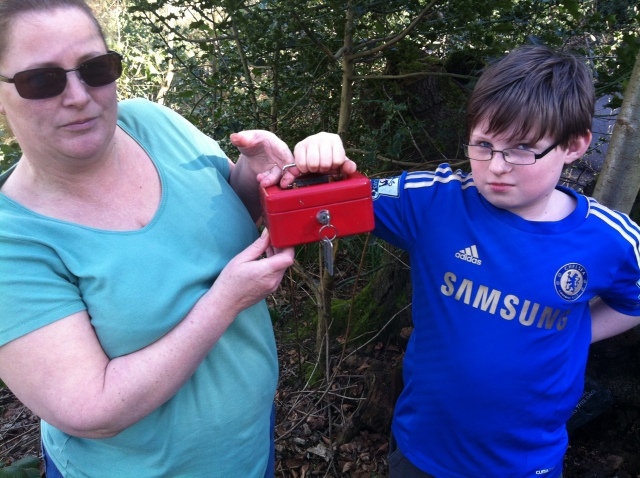 Sam and Shar pose for the camera holding the metal cash box with the key in the lock.