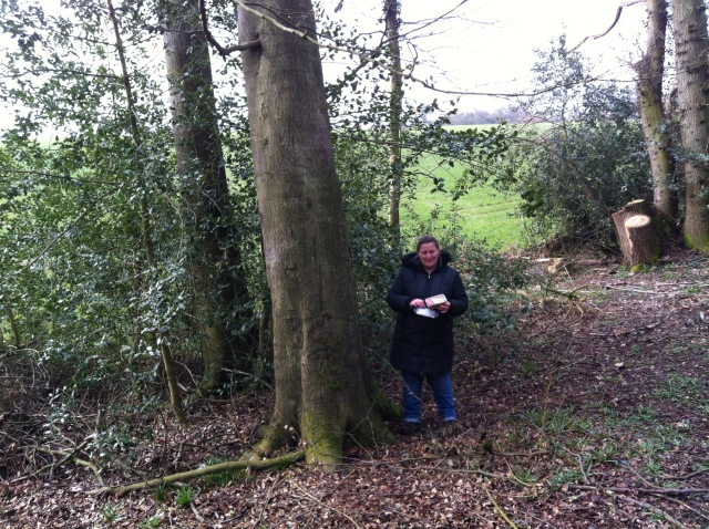Shar stands before a large tree that has just revealed the case to be hidden at its base.