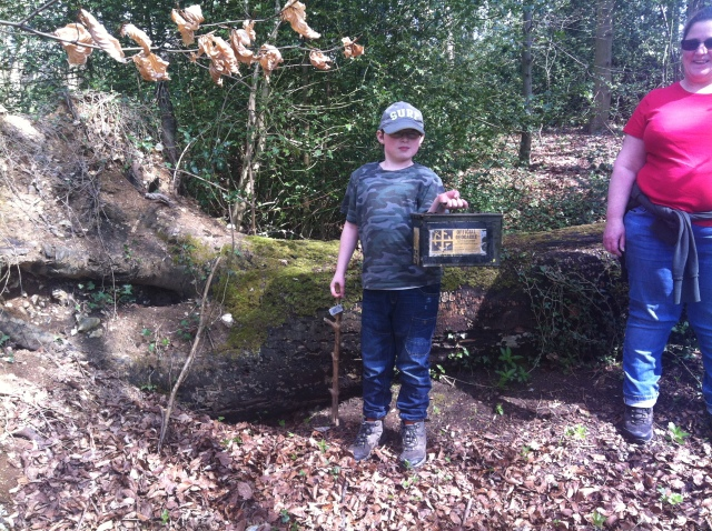 Sam sits on the fallen tree holding the cache, an Ammo Can