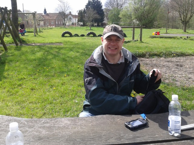 Paul sits at teh picnic table with teh playground in teh background in East Lexham