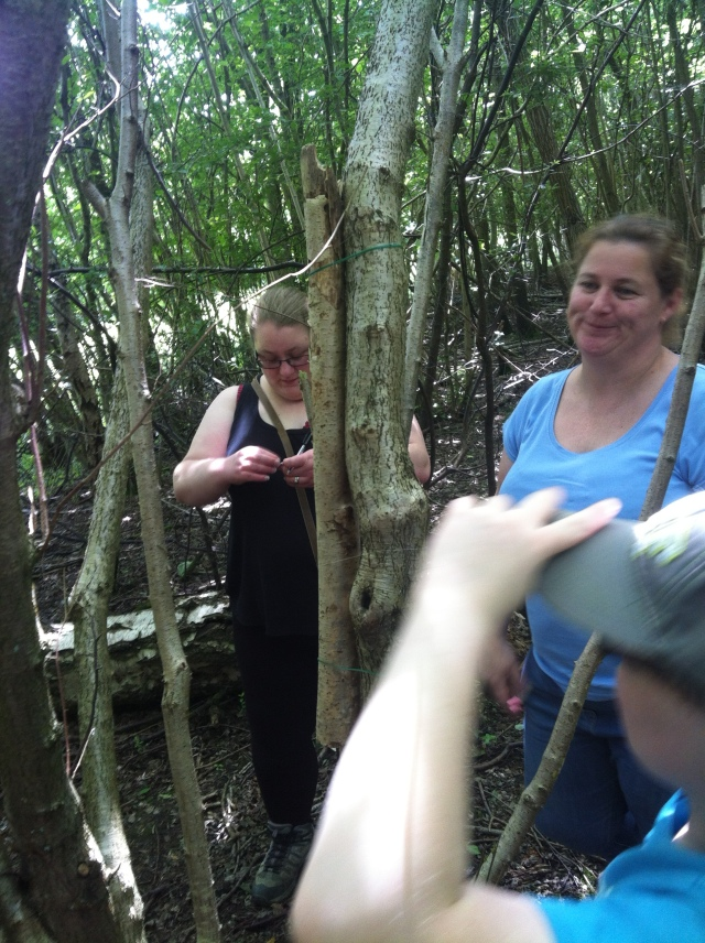 The cache is hidden inside a thin branch that has been attached to another branch using fishing line. Shar inspects the cache as Sam and Melissa look on.