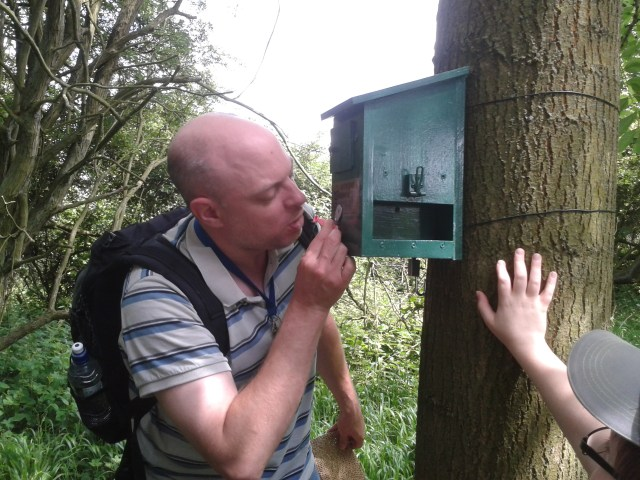 Paul is pictured feeding an uninflated balloon into a small hole on teh front of a bird box like hide.