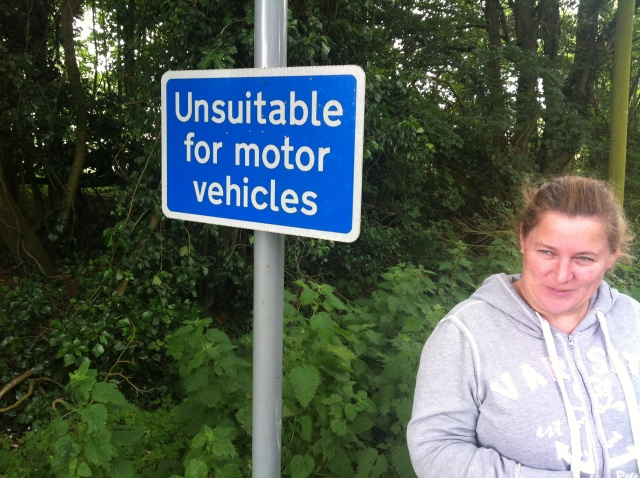 "Sharlene is picture standing on a country lane next to a sign that states ""Unsuitable for Motor Vehicles"""