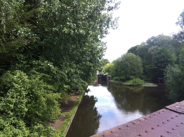 This is a view taken from the bridge out along the canal towards a lock in the distance.