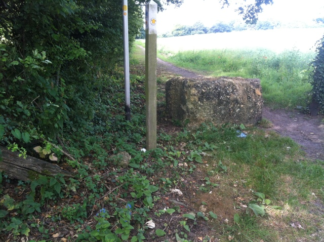 A huge boulder stands in the entrance to the footpath from the lane