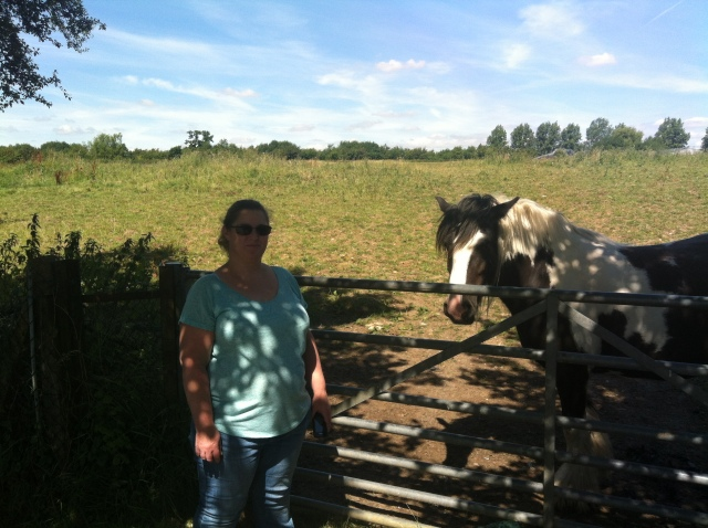 Sharlene is pictured standing in front of a metal fence. Beyond the fence and to her left is a horse.