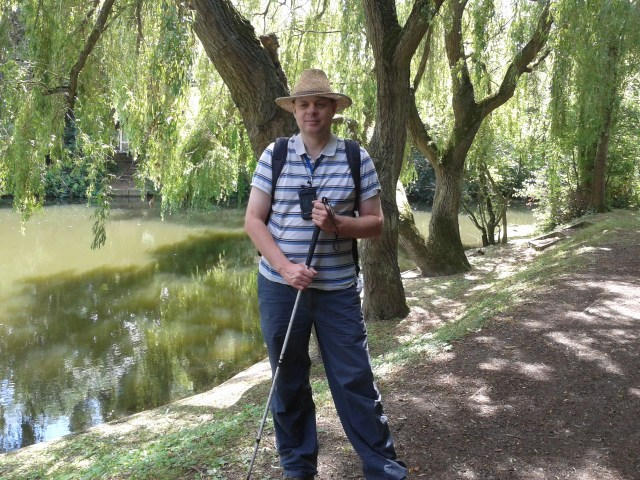 Paul is pictured standing on a footpath next to teh river colne. The trees are displaying their full summer colours and he looks happy and hot.