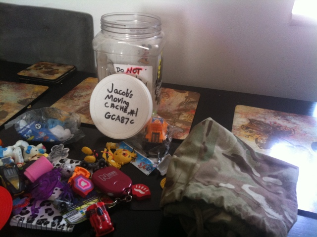 The cache container approx the size of a large sweet jar, is open on the table wiht all sorts of swag piled in front of it.