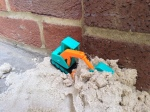 Duncan is a small plastic digger. It is posed on top of a pile of sand ready to dig.