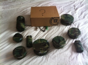 The image shows a lot of geocaches laid out. They are all covered in camoflauge tape. In the centre at the top is a box with a question mark on it covering two of the caches from view.
