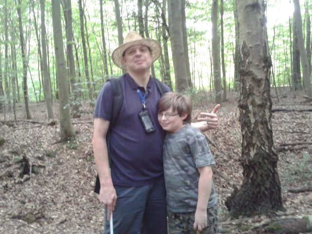 Sam and Paul stand together in the woods. Paul is making silly hand gestures behind Sam's head without him knowing.