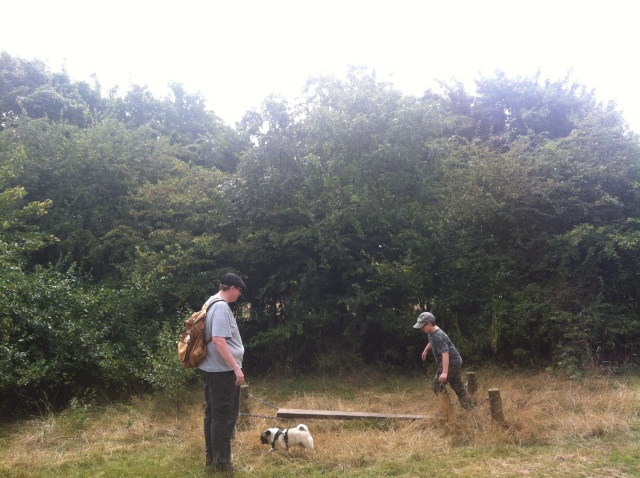 Sam is pictured walking across a balance beam as Geoff watches. Smokey is nearby