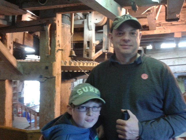 Paul and Sam pose in front of the large milling equipment. The wooden frame surrounding the grinding millstones looks old and aged.
