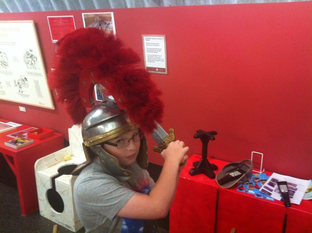 Sam poses dressed in a large centurion helmet and holding a sword.