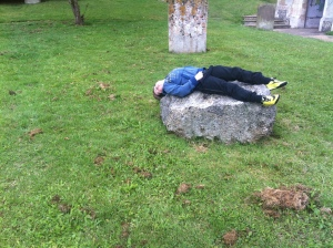 Sam lays on the lump of pudding stone in the Churchyard