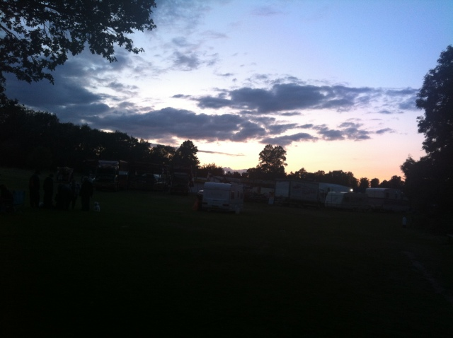 The clouds in the sky are lit by the setting sun which has thrown the fairground in teh foreground into silhouette