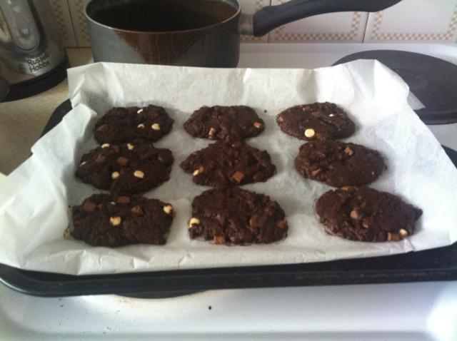 A baking tray is covered in freshly baked delicious cookies, irregular in shape but brimming with white and dark chocolate chips