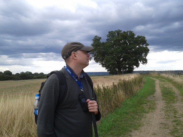 Paul stands with a lone tree and dark foreboding clouds gathering all around. He stares off to his left into the distance with a contemplative expression on his face.