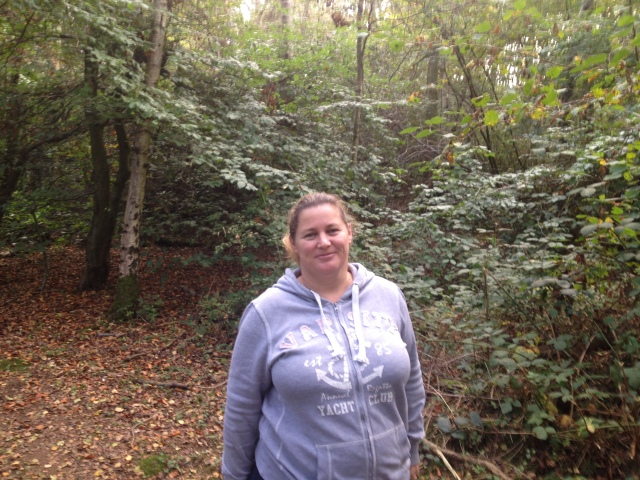 Paul stands smiling in the woods. The Autumn colours can be seen on the trees and bushes all around