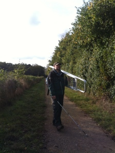 Paul strides out along a grass covered footpath shouldering a large metal step ladder