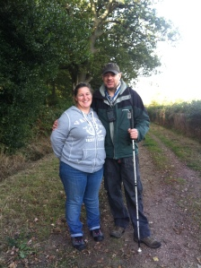 Shar and Paul Pose on the grassy footpath beside the woods