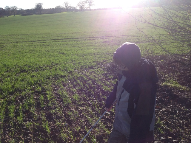 Sam stands looking cold in a field with nothing around himj for as far a the eye can see.