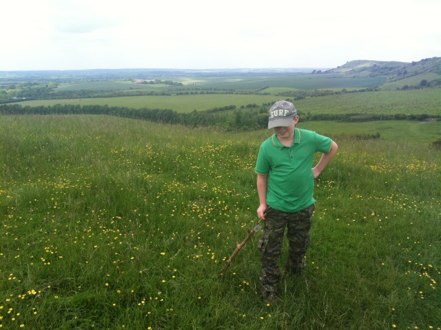 Sam stands on a hill with a scenic view of Ashridge in the background