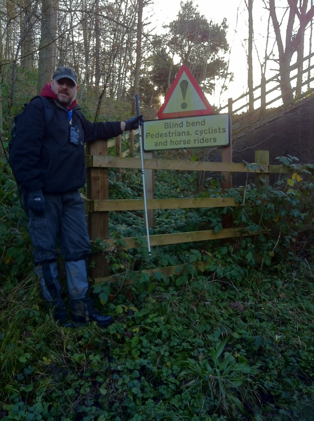 Paul is standing next to a sign that warns of a blind corner ahead