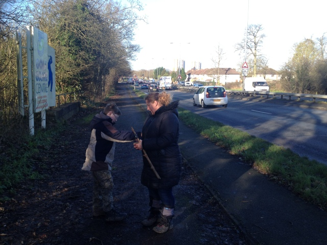 Sam and Shar stand next to a busy road on their right. Sam is doing something weird with his stick