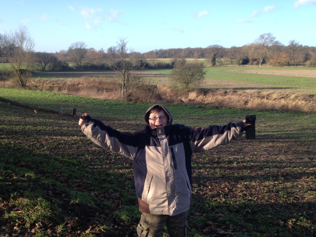 Sam stands on a footpath with fields in the background. In the distance can be seen the trees of the munden estate. He is standing with his arms stretch out wide.