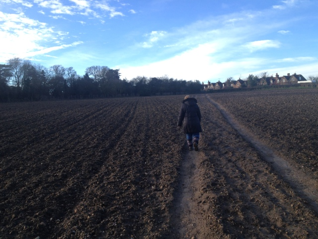 Sharlene is walking away from the camera across a muddy field. It is obviously winter and looks cold and windy.