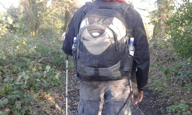 Paul stands on a muddy footpath facing away from the camera. Mud can be seen on the back of his trousers, jacket and backpack.