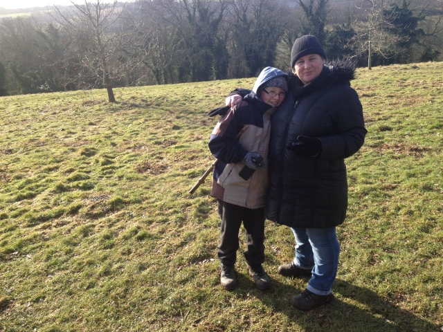 Sam and Sharlene stand close together with the park stretching out behind them. A hint of distant view can be glimpsed